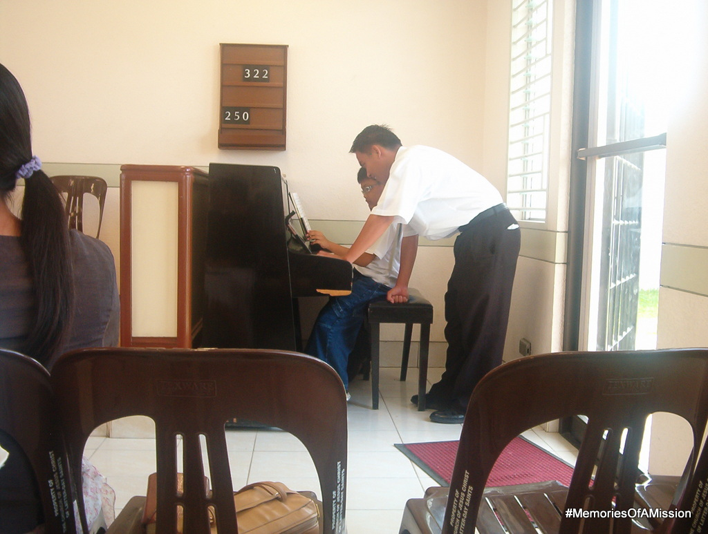 "Elder Nemes ""helping"" a boy with the piano"